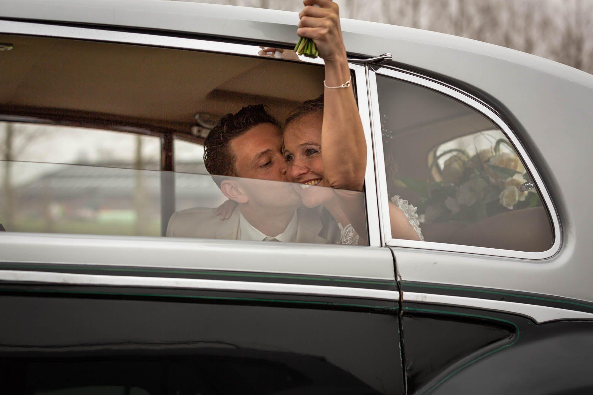 Vrolijke actiefoto bruidspaar op de snelweg.
