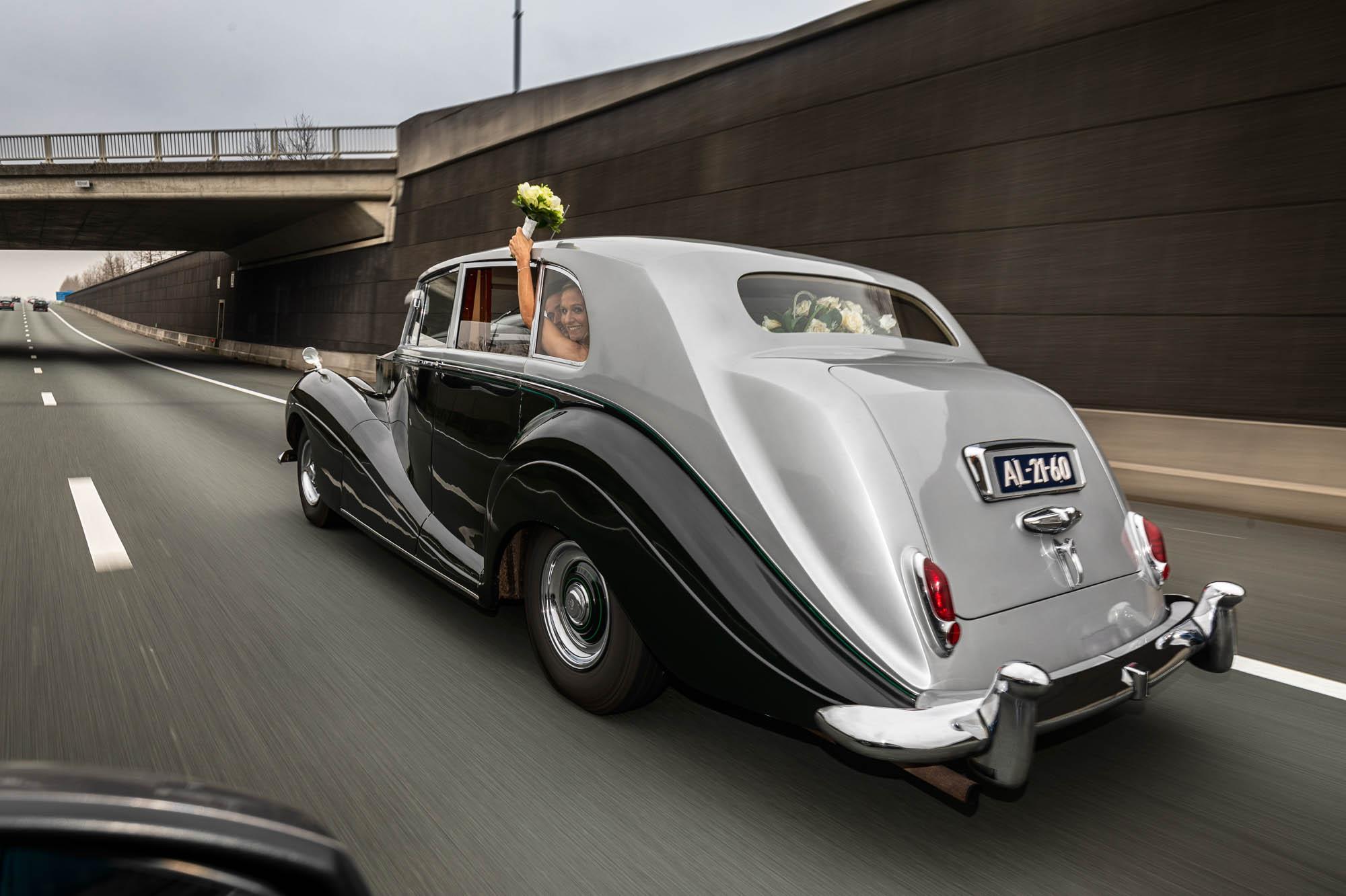 Rolls Royce op weg met bruidspaar tijdens de trouwdag.