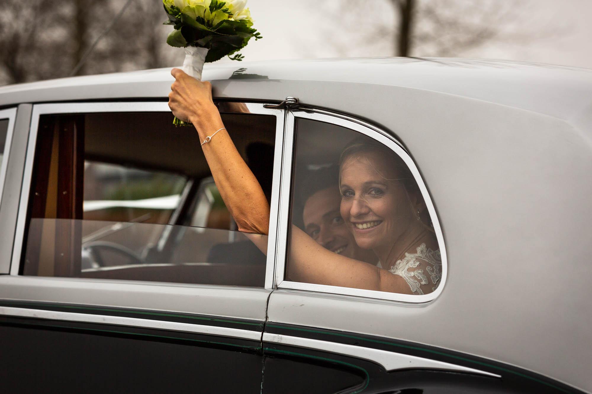 Actiefoto bruid in Rolls Royce tijdens de trouwdag.